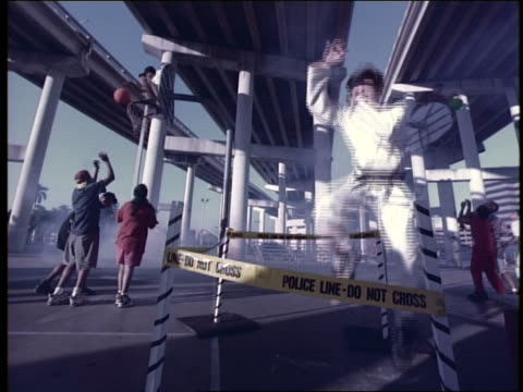 vidéos et rushes de blue slow motion boy doing karate by police line under freeway as boys play basketball in background - karaté