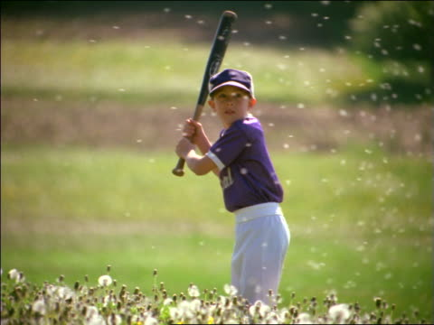 slow motion boy in little league uniform swinging at baseball in field of dandelions - baseball bat stock videos & royalty-free footage