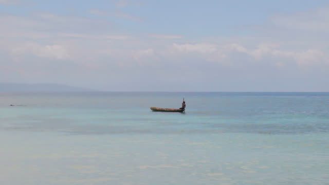 slow motion: boy paddling dugout canoe on wide blue ocean - dugout stock videos & royalty-free footage