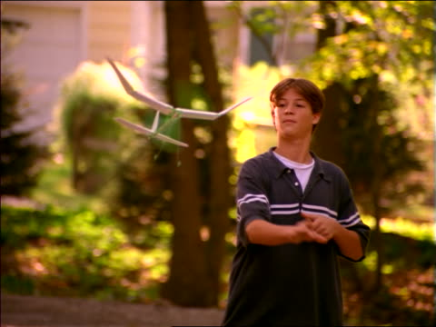 slow motion boy standing outside throwing toy airplane with spinning propeller