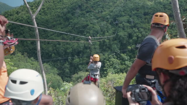 slow motion: boy taking off from ziplining platform with other people looking on in el limon, dominican republic - dominican republic stock videos and b-roll footage