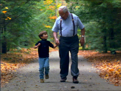 slow motion boy with grandfather holding hands skipping on country road toward camera / Autumn /Connecticut