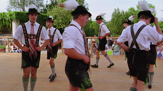 slow motion boys in german costumes dance on stage in park / bad kohlgrub, bavaria, germany - baviera video stock e b–roll