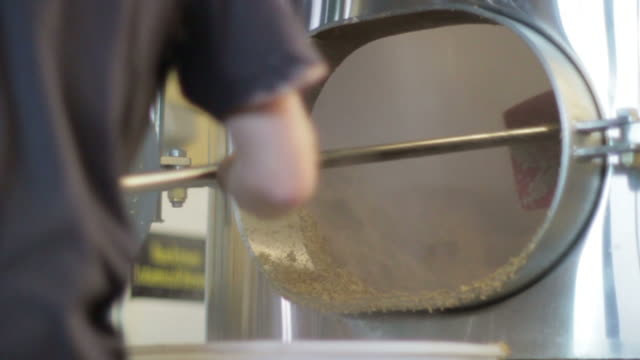 Slow motion brewery worker cleaning barley with hoe.