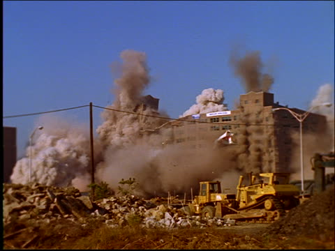 vidéos et rushes de slow motion building imploding and collapsing / demolition - imploding