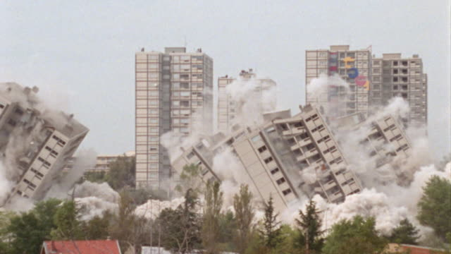 vidéos et rushes de slow motion buildings imploding and collapsing / demolition - imploding
