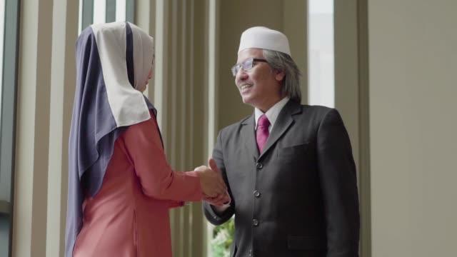 zeitlupe: geschäftsmann und muslimische frau gruß und im gespräch mit lächeln - islam stock-videos und b-roll-filmmaterial