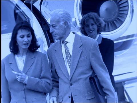 b/w slow motion businessman and woman talking by jet / stewardess in background - 男性と複数の女性点の映像素材/bロール