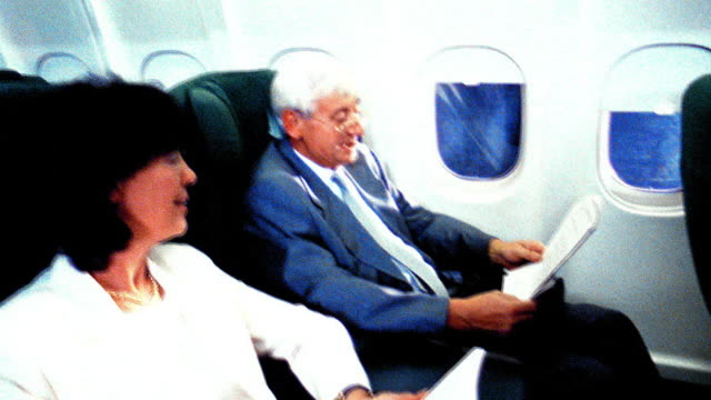 OVEREXPOSED slow motion businessman reading document + talking to woman reading book on airliner
