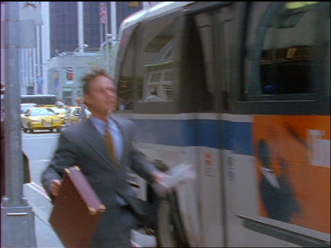 slow motion PAN businessman running to catch bus on NYC street / he misses bus