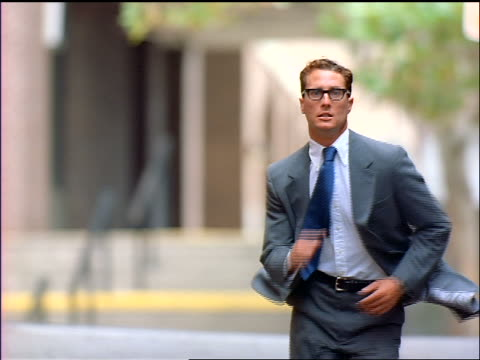 slow motion businessman running towards camera + looking at watch - suit stock videos & royalty-free footage
