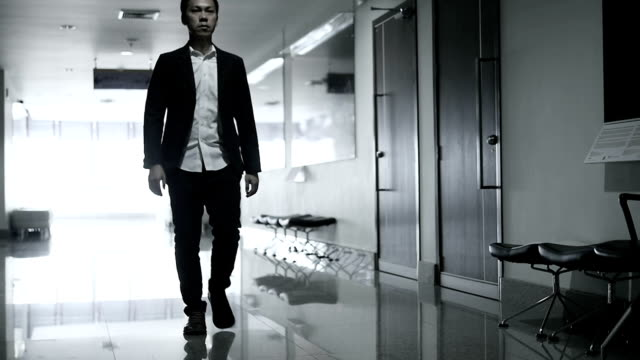 HD : Slow motion Businessman walking in office building