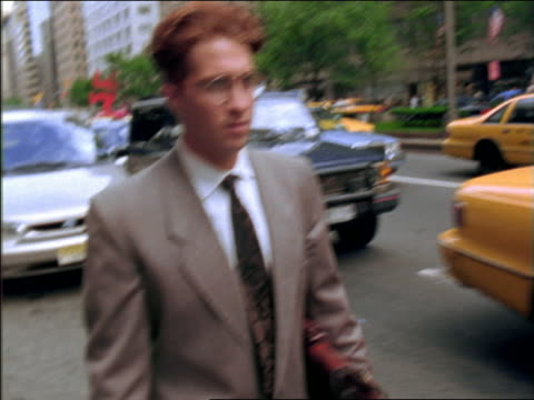 slow motion pan businessman walking past stopped traffic on park avenue / nyc - only mid adult men stock videos & royalty-free footage