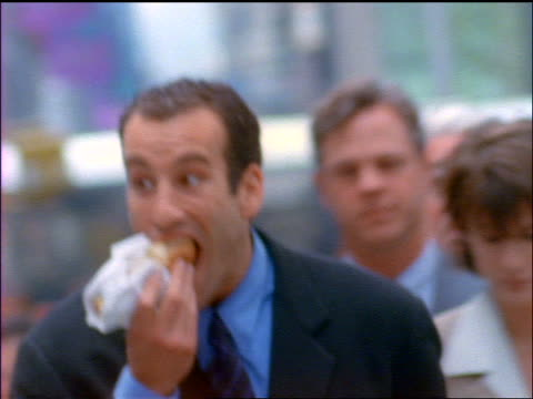 vídeos de stock, filmes e b-roll de slow motion businessman walks toward cam on nyc street eating hot dog + checking his watch - camisa e gravata