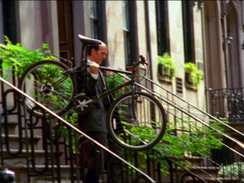 slow motion businessman with briefcase walking down steps of brownstone carrying mountain bike / rides - nur männer über 30 stock-videos und b-roll-filmmaterial