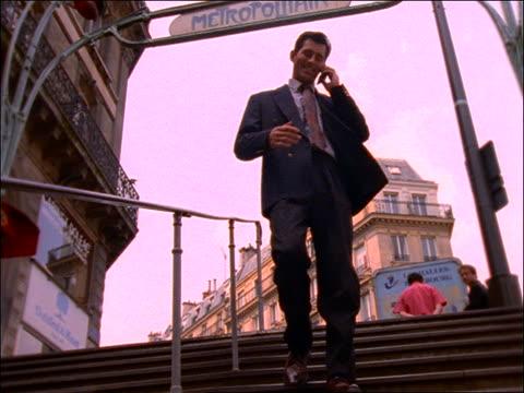 vídeos de stock, filmes e b-roll de slow motion businessman with cellular phone  on metro stairs / paris - 1990