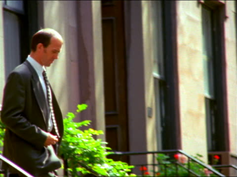 slow motion businessman with keys walking down steps of brownstone / puts keys in pocket / brooklyn heights - nur männer über 30 stock-videos und b-roll-filmmaterial