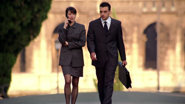 slow motion businessman + woman walking toward camera with Colosseum in background / woman on cellular phone / Rome