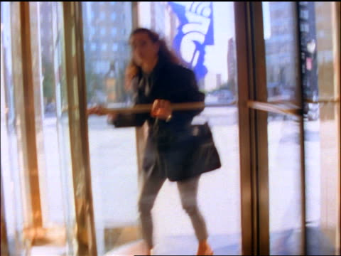 slow motion businesswoman entering office building through revolving door - revolving door stock videos & royalty-free footage