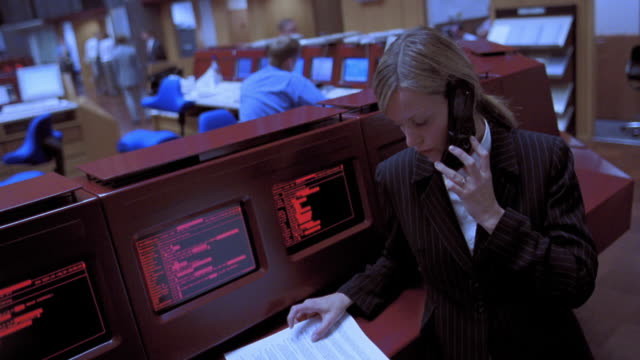 blue canted slow motion pan businesswoman reading report over cell phone / frankfurt stock exchange - frankfurt stock exchange stock videos and b-roll footage