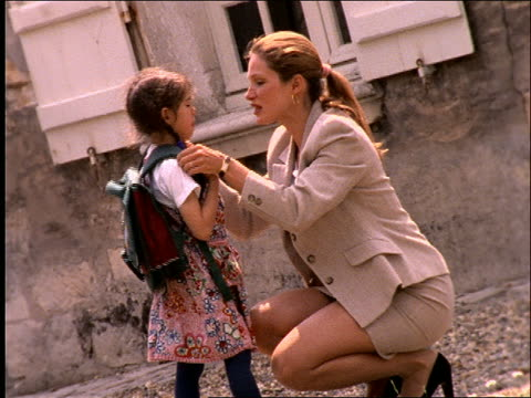 slow motion businesswoman talking to young schoolgirl / Paris