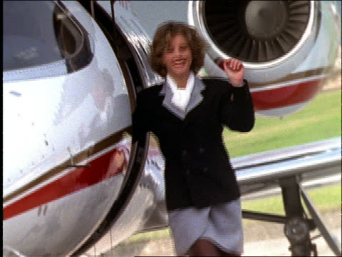 slow motion businesswoman waving from jet and walking toward cam - 1997 stock-videos und b-roll-filmmaterial