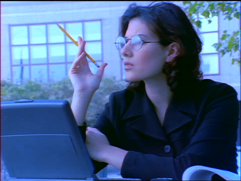 BLUE slow motion businesswoman working thoughtfully on laptop outdoors / she bites pencil + types