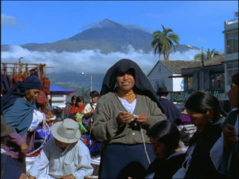 slow motion pan busy outdoor indian textile market / mountains in background / otavalo, ecuador - ecuadorian ethnicity stock videos and b-roll footage