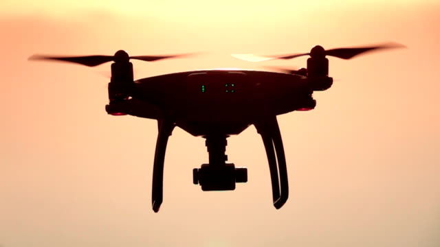 vídeos de stock e filmes b-roll de slow motion: camera drone hovering in the sky at sunset - pairar