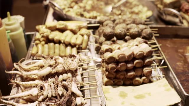 vidéos et rushes de slow motion: camera pans over various foods on skewers at outdoor vendor - marché
