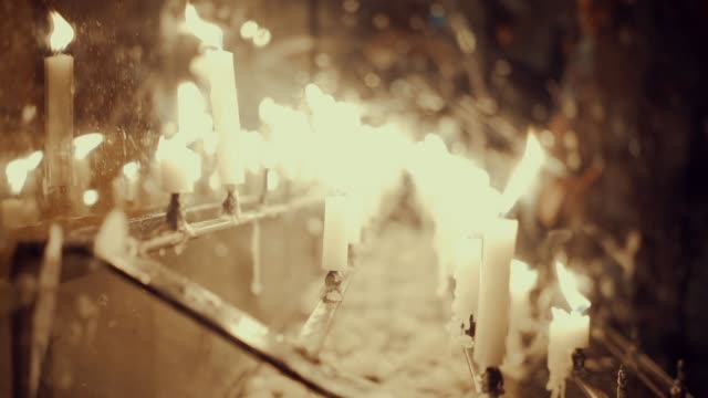 slow motion candles in church in low light. burning candles inside the church. - altare video stock e b–roll