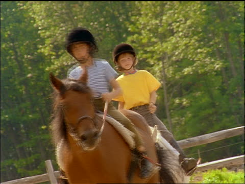 slow motion canted 2 girls wearing riding gear on horseback trotting towards camera - freizeitreiten stock-videos und b-roll-filmmaterial