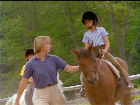 slow motion canted 2 girls wearing riding gear on horseback / instructor walks next to them - recreational horseback riding stock videos & royalty-free footage