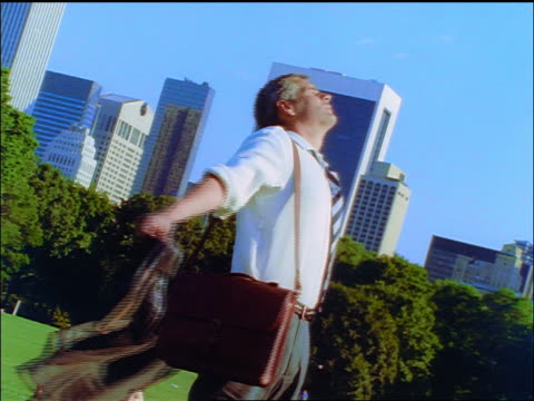 slow motion canted businessman carrying his shoes spinning in sheep's meadow of central park / nyc - one mid adult man only stock-videos und b-roll-filmmaterial