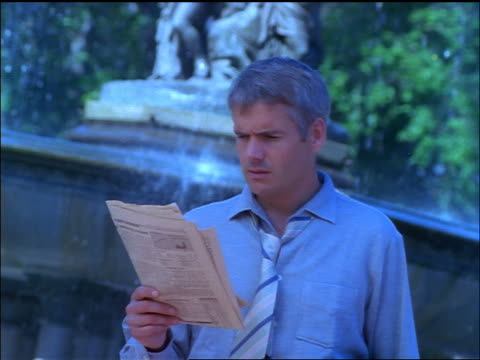 BLUE slow motion CANTED businessman walks in front of fountain looking at newspaper + gets upset / NYC