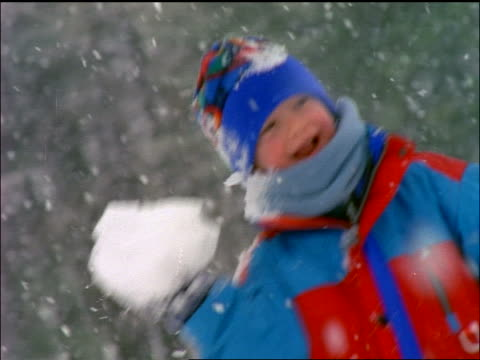 stockvideo's en b-roll-footage met slow motion canted close up boy throwing snowball in snowstorm - alleen jongens