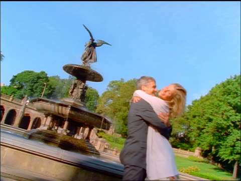 vídeos de stock e filmes b-roll de slow motion canted couple hugging + spinning in front of bethesda fountain / central park, nyc - fonte bethesda
