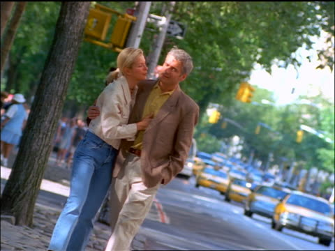 stockvideo's en b-roll-footage met slow motion canted couple hugging + talking while walking on nyc sidewalk - zij aan zij