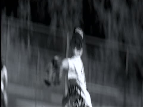 B/W slow motion CANTED PAN from Little League pitcher to baseball bat swinging