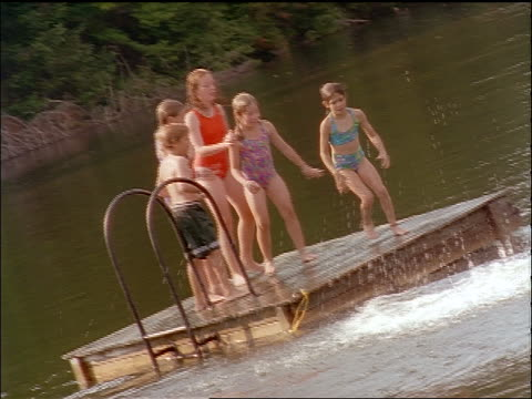 slow motion canted group of children jumping from dock into lake one at a time - one piece swimsuit stock videos & royalty-free footage