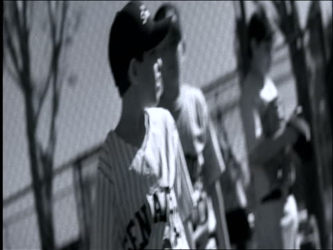 vidéos et rushes de b/w slow motion canted pan little league baseball players walking past camera onto field - casquette de baseball