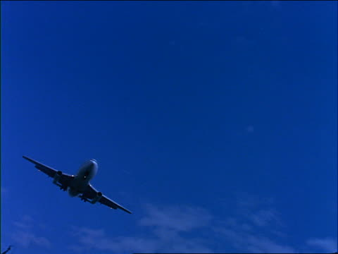 stockvideo's en b-roll-footage met slow motion canted low angle airliner descending over camera / blue filter - 1990