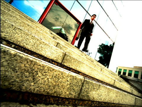 vidéos et rushes de overexposed slow motion canted low angle businessman runs down steps in front of modern building + checks watch - overexposed