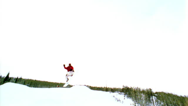 overexposed slow motion canted low angle long shot pan snowboarder jumping off of half pipe / resort + mountains in background - half pipe stock videos & royalty-free footage