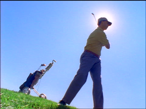 slow motion canted low angle male golfer with sun behind head swings + hits unseen ball - maglietta polo video stock e b–roll