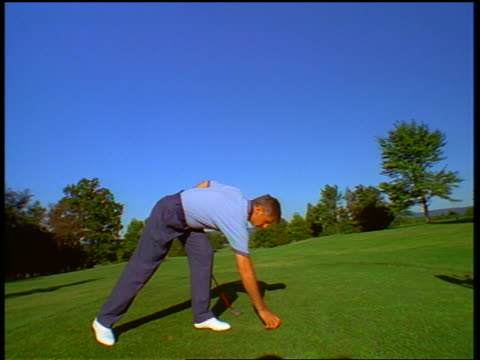 vídeos y material grabado en eventos de stock de slow motion canted middle aged male golfer sticking tee into ground + teeing off / trees + blue sky in background - zapato de golf