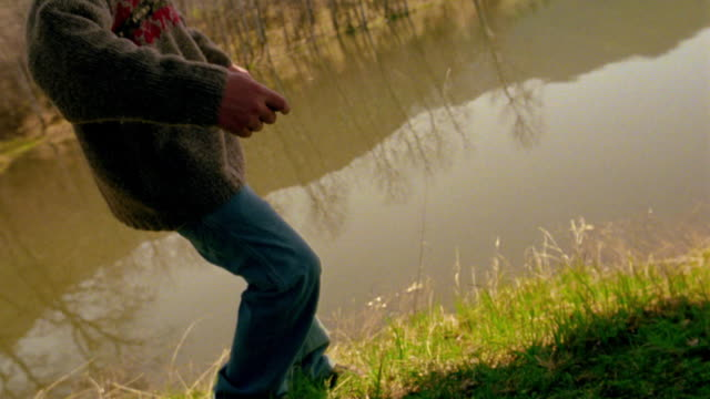 slow motion CANTED point of view toward boy (head not visible) throwing/skipping stone into pond / Montana