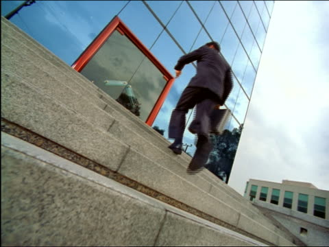slow motion CANTED REAR VIEW low angle businessman runs up steps, checks watch + enters modern mirrored building