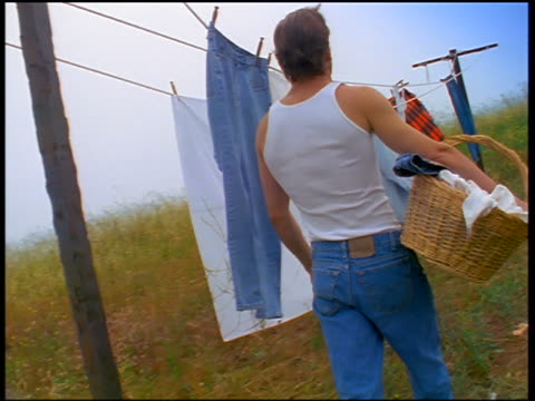 stockvideo's en b-roll-footage met slow motion canted rear view tracking shot man wearing undershirt + jeans carrying basket + walking past clothesline - wasmand