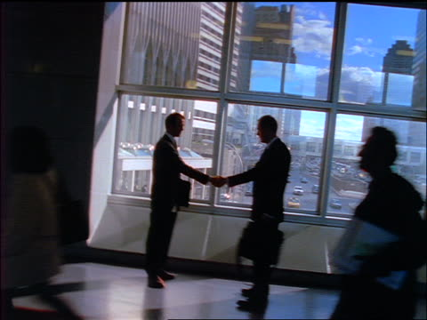 vidéos et rushes de slow motion canted silhouette of two businessmen talking + shaking hands in nyc office bulding - manhattan
